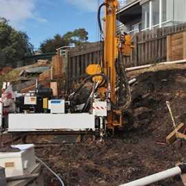 Geotechnical drilling at the head scarp of a landslide undermining a house in southern Tasmania.
